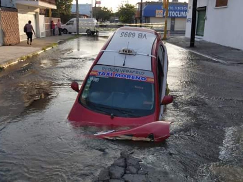 Cae taxi en socavón y provoca fuga