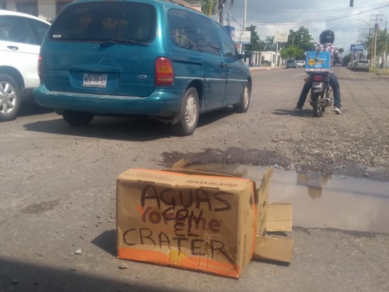 Comerciantes alertan a conductores por baches