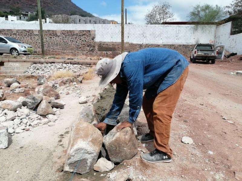 Construyen muro de piedra braza en las 100 Casas