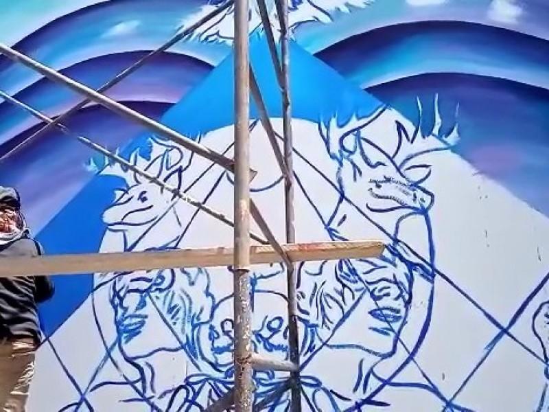 Joven muralista plasma su obra en plaza pública