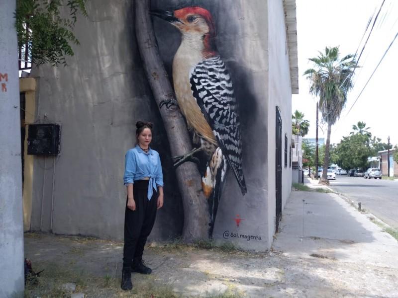 Joven pinta mural de un pájaro carpintero