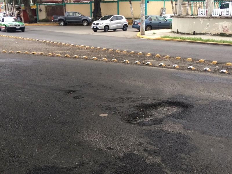 Reportan baches en avenida recien asfaltada