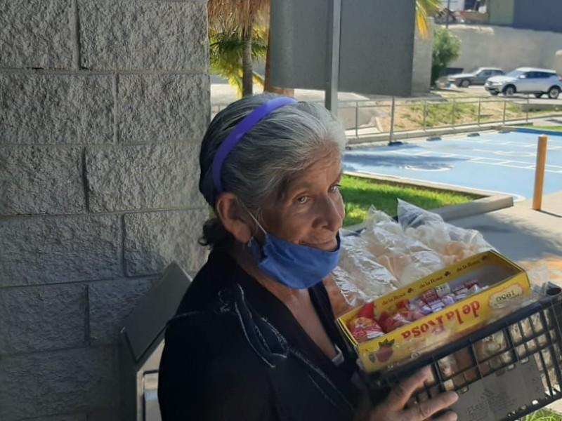 Señora de la tercera edad vende dulces para subsitir
